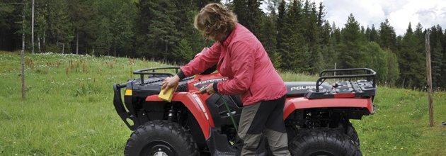 Kvinna tvättar fyrhjuling med en svamp.