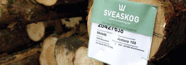 Fasthäftad Sveaskog-etikett på timmer.